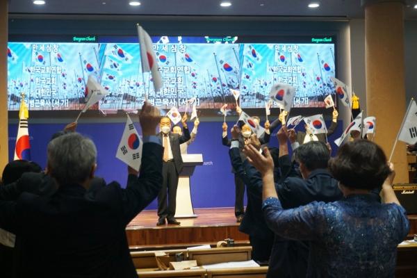 한교연 주요 인사들이 태극기를 들고 만세삼창을 하고 있다.
